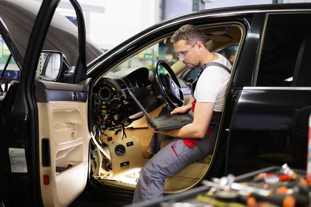 Serviceman making car diagnostics with laptop in a workshop Фото со стока