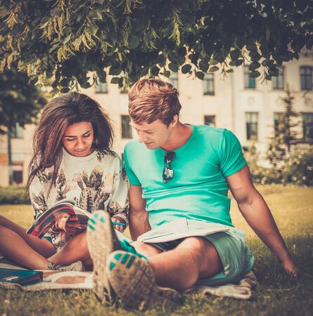Multi ethnic students couple preparing for final exams in a city park  photo