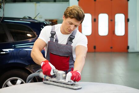 Young serviceman performing grinding with machine on a car bonnet in a workshop photo