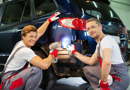 Two workers with colour samples choosing correct shade in a car body workshop  photo
