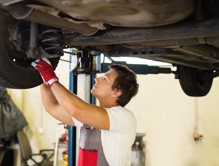 Serviceman checking suspension in a car workshop  Stock Photo