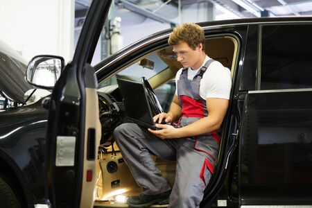 Serviceman making car diagnostics with laptop in a workshop photo