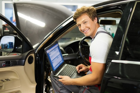 Serviceman making car diagnostics with laptop in a workshop photo