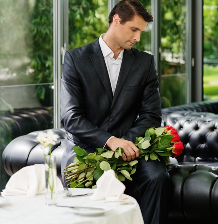 Handsome man with bunch of red roses waiting his lady in restaurant  photo