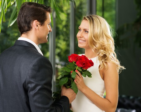 Handsome man with bunch of red dating his lady photo