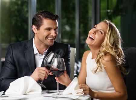 diner romantique: Cheerful couple dans un restaurant avec des verres de vin rouge