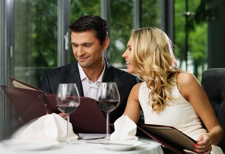 carte: Cheerful couple with menu in a restaurant