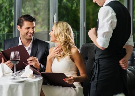 Vrolijk paar met menu in een restaurant