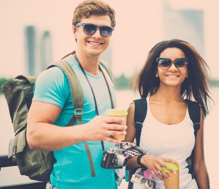 Multi-ethnic couple tourists with map and coffee cups near river in a city photo