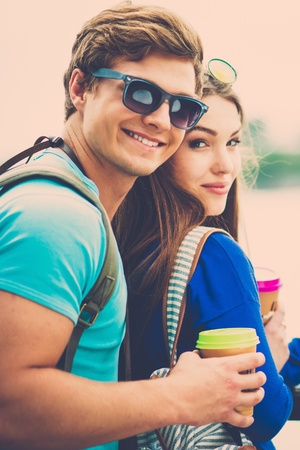 Couple tourists with map and coffee cups near river in a city photo