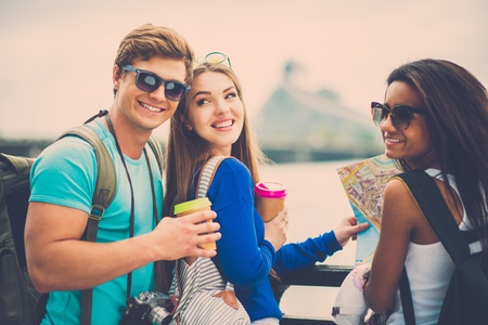 Multi-ethnic friends tourists with map and coffee cups near river in a city photo