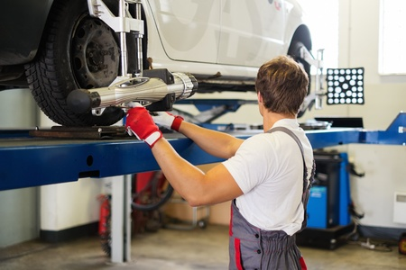 Young serviceman checking wheel alignment  in a car workshop  Stock Photo