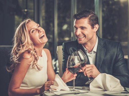 赤ワインのガラスを持つレストランで陽気なカップル