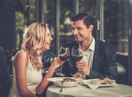 Vrolijk paar in een restaurant met glazen rode wijn Stockfoto
