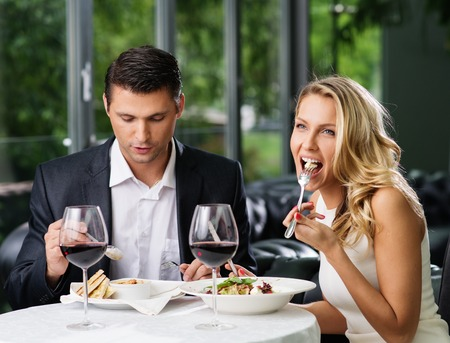 Couple eating in restaurant with a red wine  Stock Photo