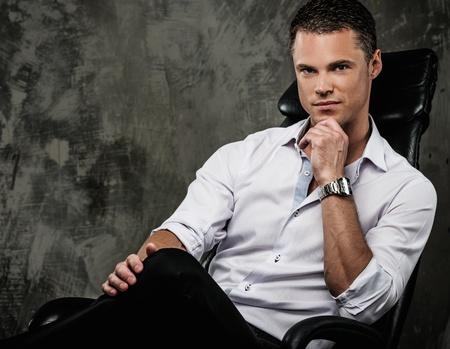 Knappe man in shirt tegen grunge muur zitten in bureaustoel Stockfoto