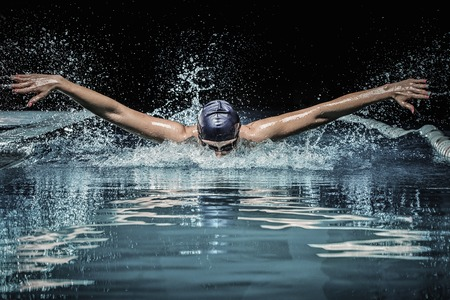 Young man in swimming cap and goggles swim using breaststroke technique Stock Photo