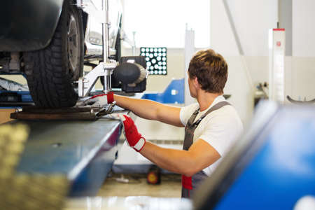 Young serviceman checking wheel alignment  in a car workshop Фото со стока - 30357439