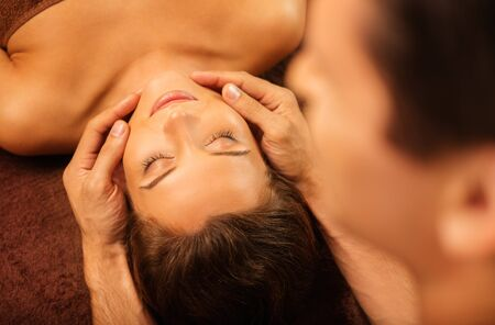 Young woman having face massage in a spa salon Zdjęcie Seryjne