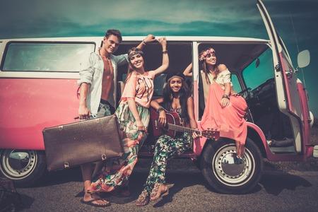 Multi-etnisch hippie vrienden met gitaar op een road trip Stockfoto