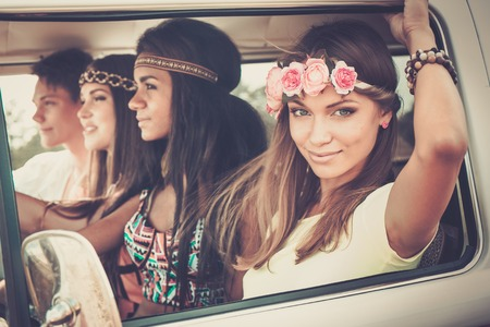 Multi-ethnic hippie friends in a minivan on a road trip