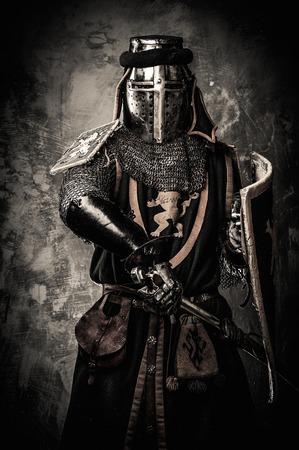Caballero medieval con una espada contra la pared de piedra Foto de archivo - 31170689