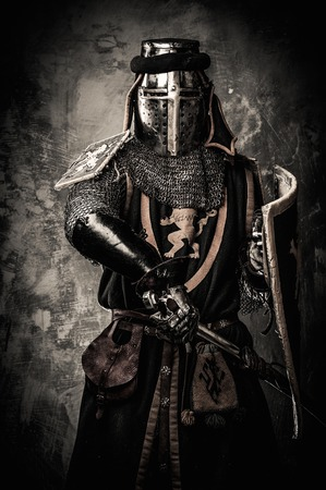 Medieval knight with a sword against stone wall Imagens