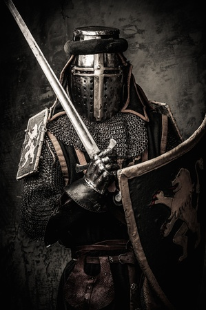 Medieval knight with a sword against stone wall Stockfoto