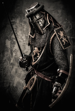 Medieval knight with a sword against stone wall Фото со стока