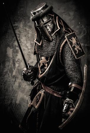 Middeleeuwse ridder met een zwaard tegen de stenen muur Stockfoto