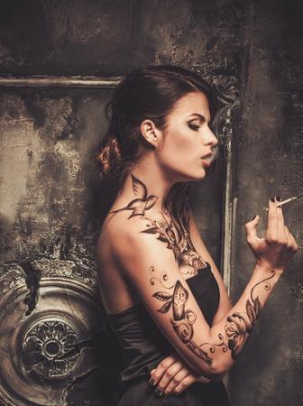 喫煙入れ墨古い不気味なインテリアで美しい女性
