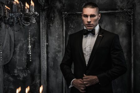 Young man wearing tuxedo in classical interior Stock Photo