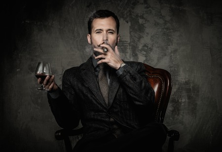Handsome well-dressed with glass of beverage and cigar Foto de archivo