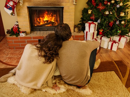 Couple near fireplace in Christmas decorated house interior  Фото со стока
