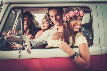 Multi-etnisch hippie vrienden in een minivan op een road trip Stockfoto