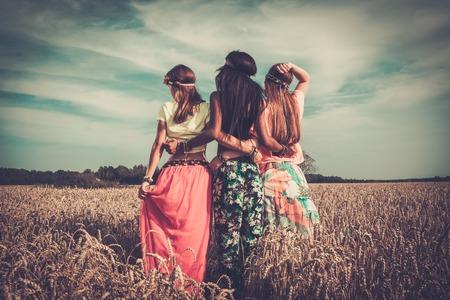 Multi-etnische hippie meisjes in een tarweveld Stockfoto - 32489241
