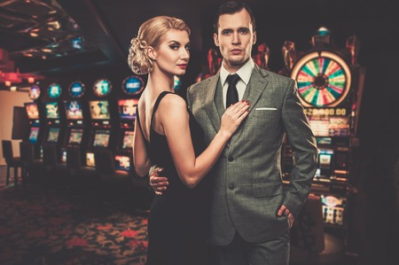 Goed gekleed paar tegen speelautomaten Stockfoto