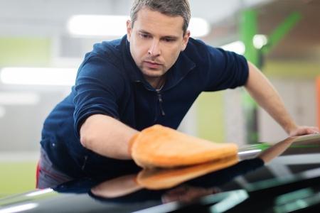 Man travailleur polissage voiture sur un lavage de voiture