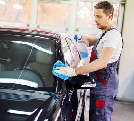 クリーニングのスプレーが付いている車の洗車で働く労働者