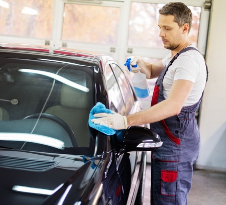 Arbeider op een wasstraat reinigen auto met een spray