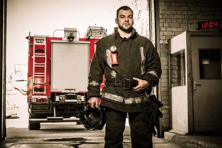 Firefighter against truck in firefighting depot