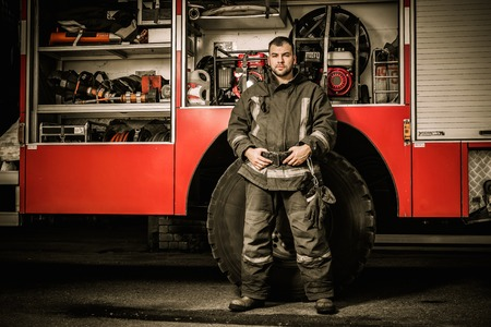 Cheerful firefighter near truck with equipment Archivio Fotografico