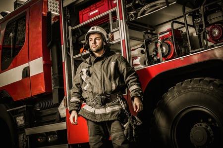 装備のトラックの近くの陽気な消防士