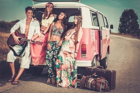 ロードト リップにギターと多民族のヒッピーの友達 写真素材