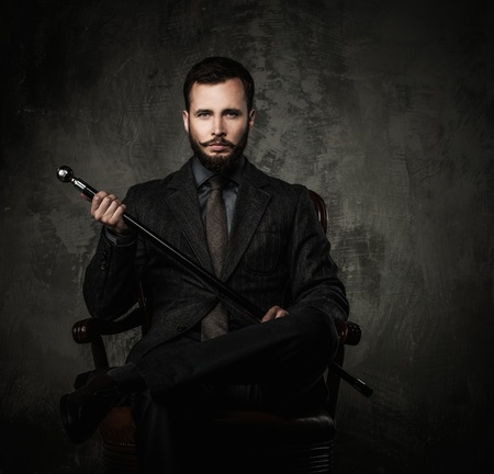 Handsome well-dressed man with walking stick sitting in leather chair Stock Photo - 33503996