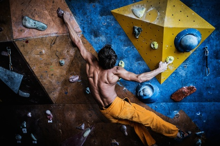 Muscular man practicing rock-climbing on a rock wall indoors Фото со стока