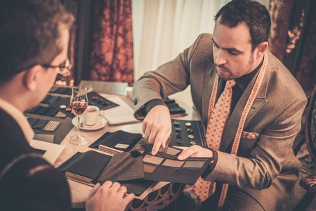 Tailor and client choosing cloth and buttons for custom made suit Imagens
