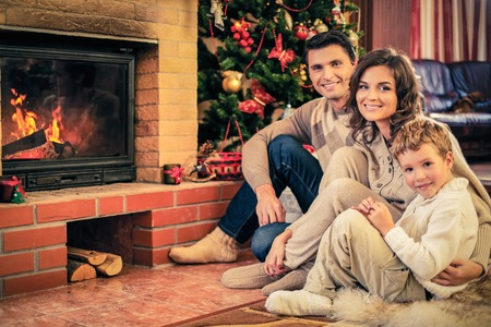 Family near fireplace in Christmas decorated house interior Stockfoto