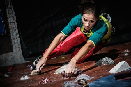 Young woman practicing rock-climbing on a rock wall indoors Banque d'images