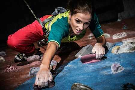 Young woman practicing rock-climbing on a rock wall indoors Stockfoto